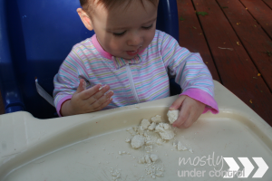 baby playing with sensory moon sand