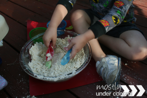 Close up of child playing with moon sand in a glass bowl with plastic utensils