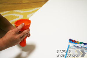 child's hand filling a balloon with beans for sensory balloons