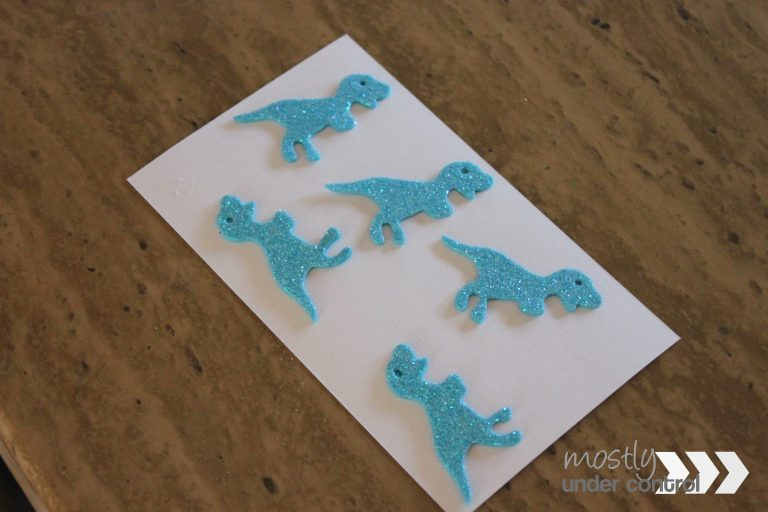 Blue glitter dinosaur foam stickers on a white notecard.