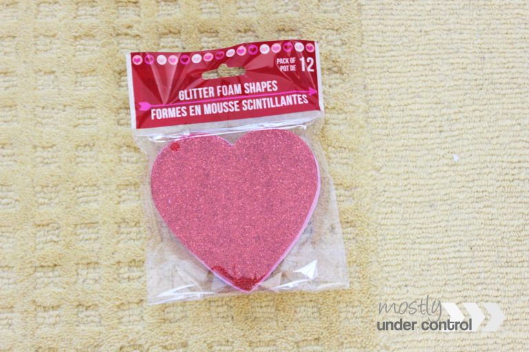 Birds eye view of a package of red glittery red hearts on a yellow rug