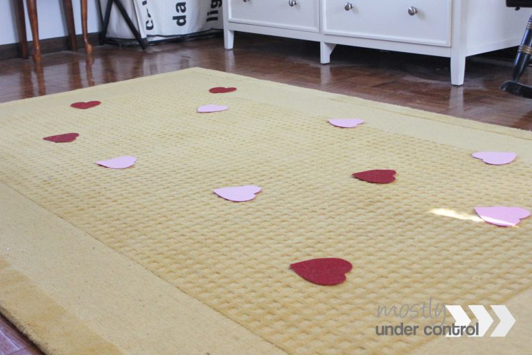 5 red hearts and 6 pink hearts spread out on a yellow rug