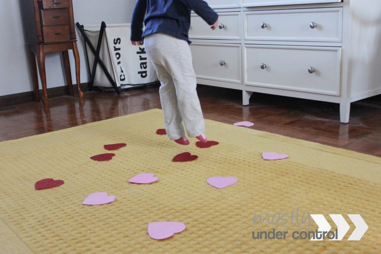 Child jumping on red and pink hearts with gray sweatpants and a navy blue long sleeved shirt.