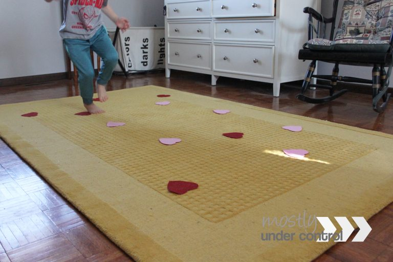 child in blue pants jumping from a red heart to a pink heart spread out on a yellow rug.