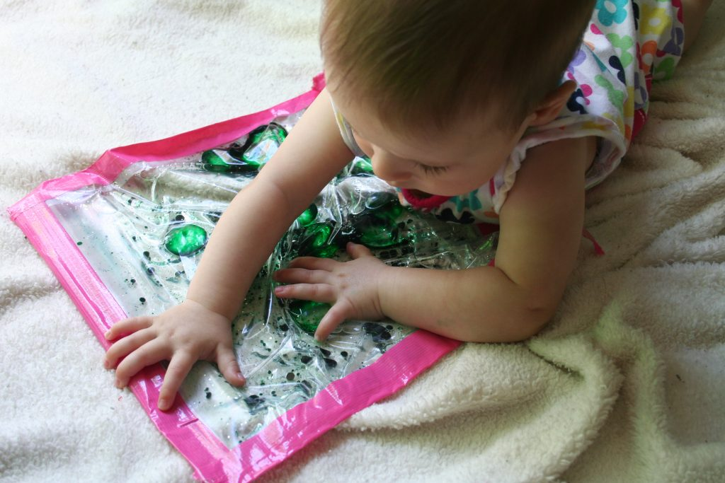 top view of baby playing with a sensory water bag with pink tape around the edges and green baby oil in the water.