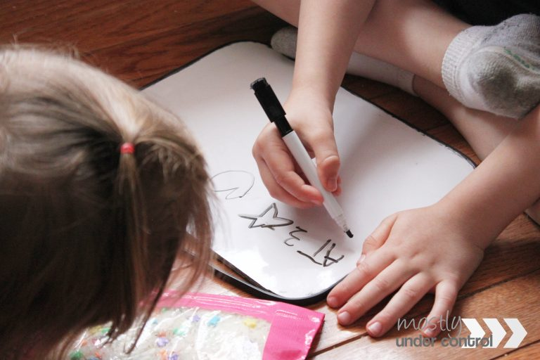 child writing down letters on a white board while searching through a toddler i-spy bag