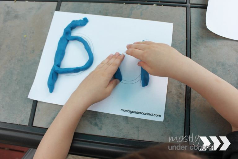 close up bird's eye view of child playing with play dough mat and blue play dough
