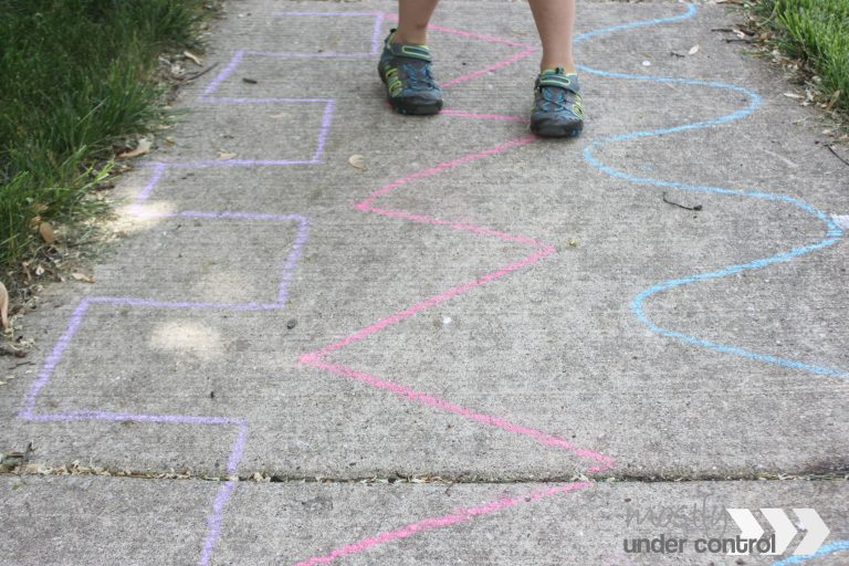 Close up of child walking on chalk lines for sidewalk chalk games