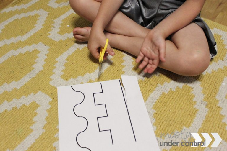Close up of child using free scissor skill cutting printable
