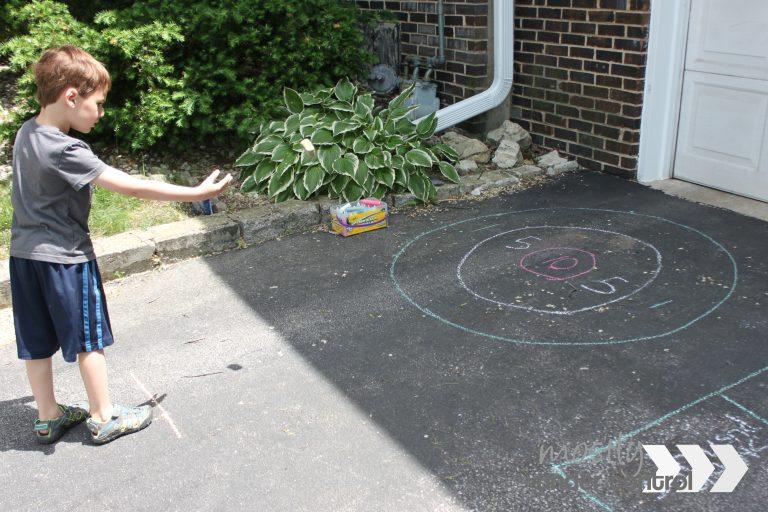 Child playing sidewalk chalk games - target practice