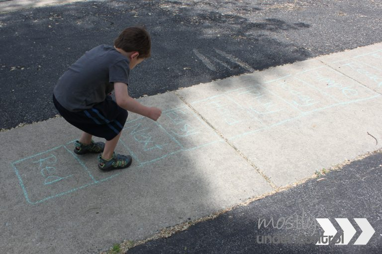 Child playing sidewalk chalk games - sight word hopscotch