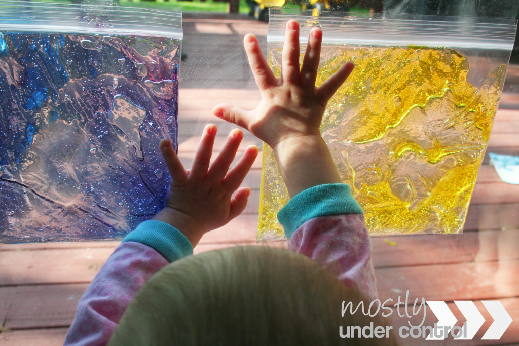Photo of a baby pressing against a yellow sensory bag with hair gel and a purple sensory bag with hair gel.