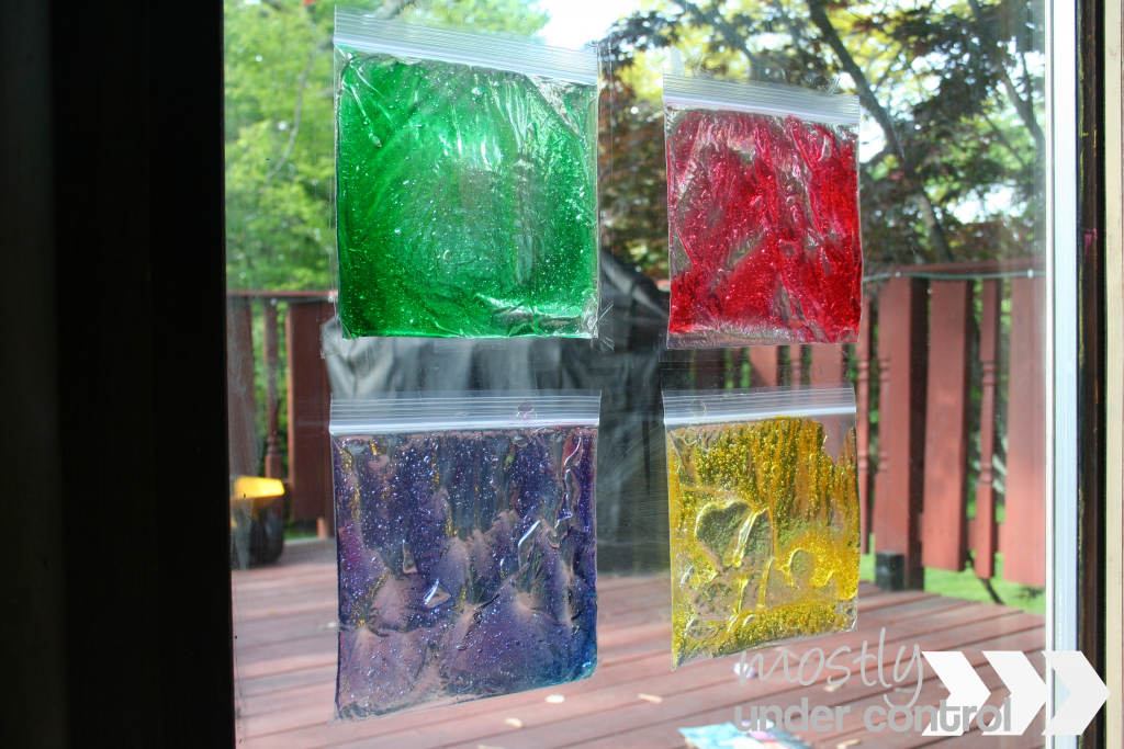 Photo of 4 sandwich bags attached to a sliding glass door filled with  green, red, purple and yellow colored hair gel.