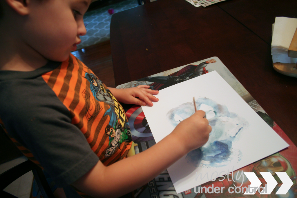 Photo of a boy coloring blue with ice cube painting on a white piece of paper.
