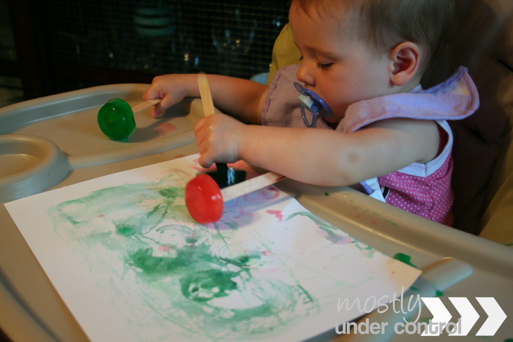 a baby at a high chair doing ice cube painting with red, green and blue on white paper.