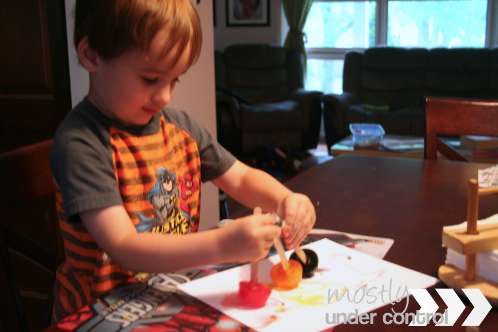 a child doing ice cube painting with red, yellow and blue ice cubes on white paper.