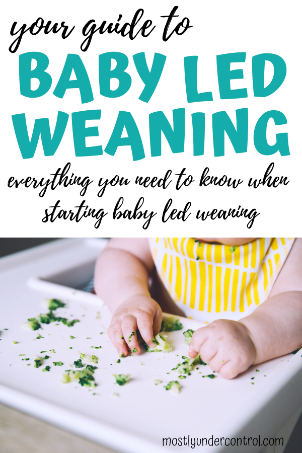 your guide to baby lead weaning. everything you need to know when starting baby led weaning. photo of baby playing in broccoli with a yellow striped bib on.