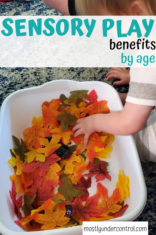 Top view of toddler playing in a sensory bin of fake fall leaves