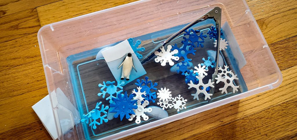 Arial view of a clear shoe box sized bin with blue water, ice cubes, blue and white foam snowflakes, white pieces of foam, plastic penguins and gray child sized tongs.