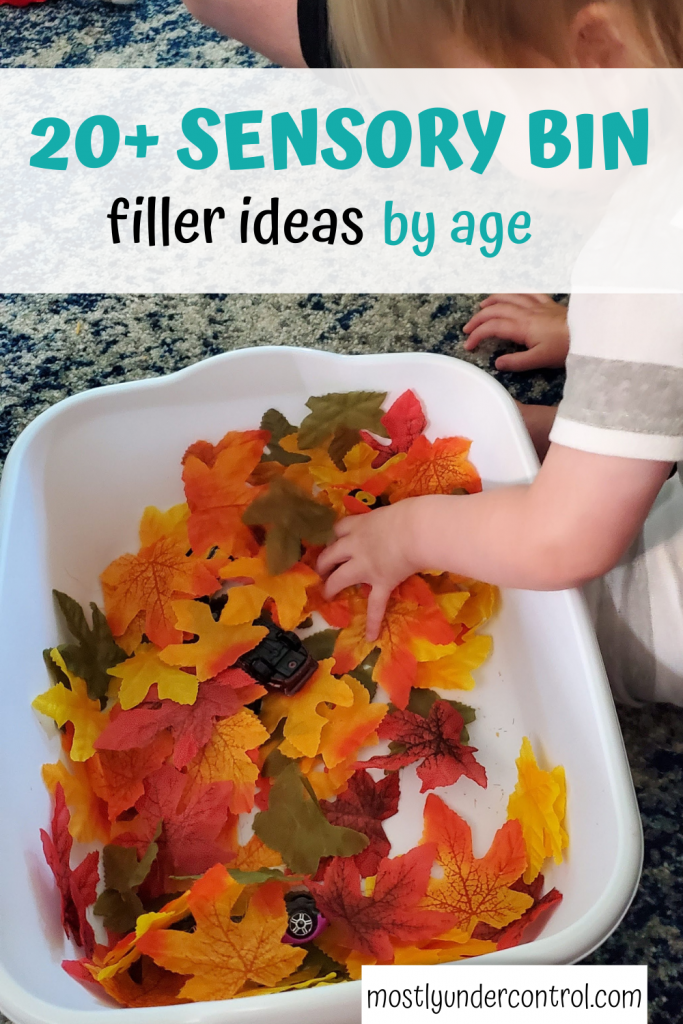 White bin filled with fake green, yellow, orange and red leaves, 2 small cars and a child's hand. Text overlay: 20+ sensory bin filler ideas by age.