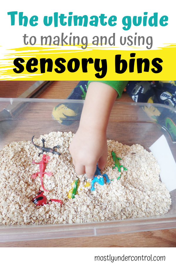Child's hand in a bin of oatmeal with colored bugs with text overlay that reads The ultimate guide to making and using sensory bins.