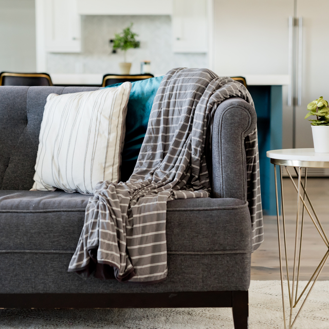 photo of a gray and white striped blanket in a gray couch