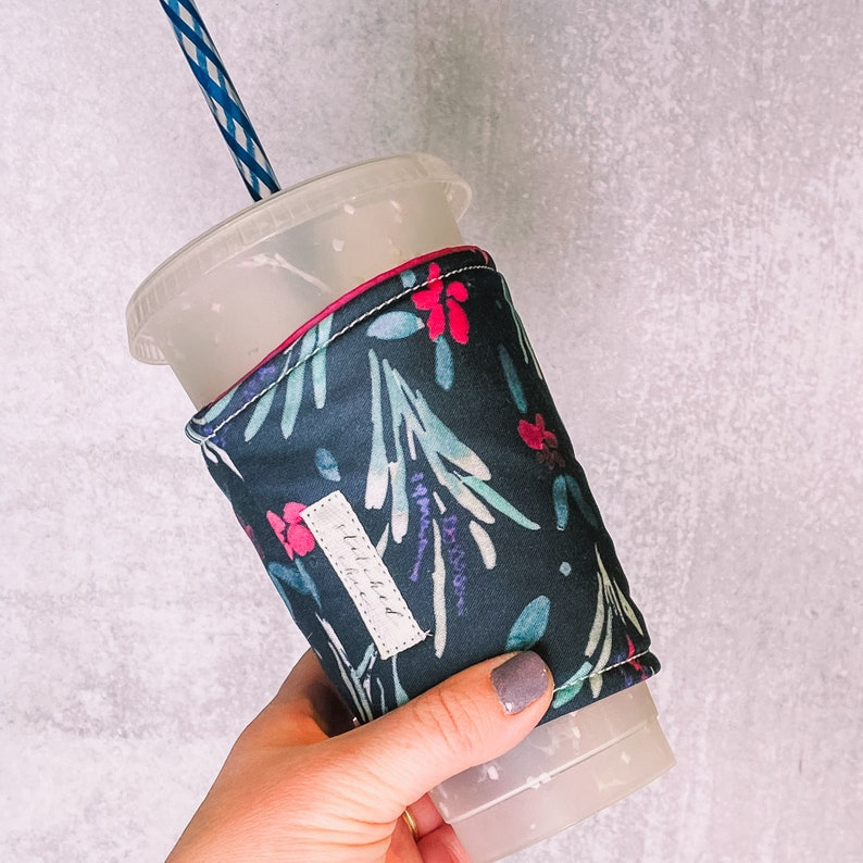 blue coffee sleeve with pink flowers around a clear coffee cup with a blue and white straw being held by a hand with gray nail polish.